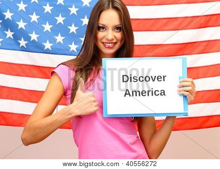 Young woman young woman holding tablet on background of American flag