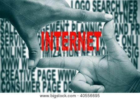 man hands making a frame with its fingers and the word internet written in red inside, on a background full of words about internet concept