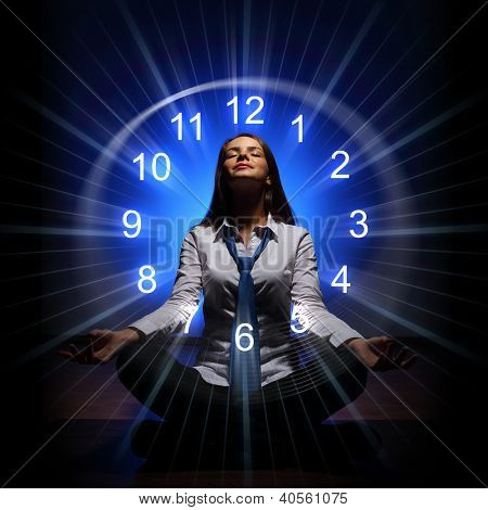 Young businesswoman sitting against blue background with clock interface