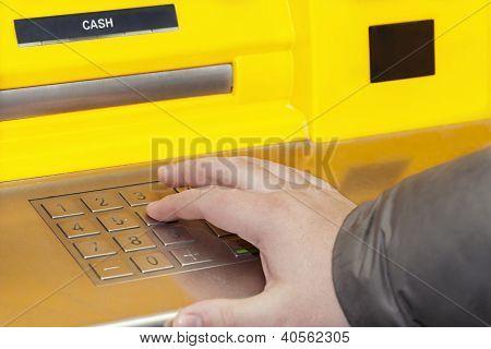 Man's hand near the cash machine on the pin code