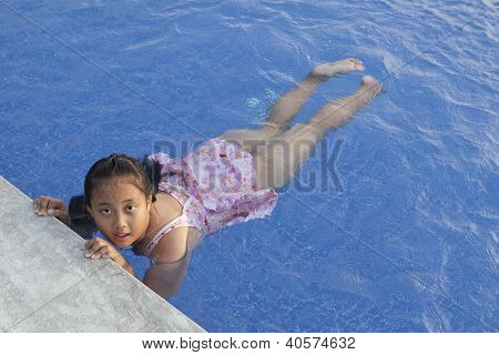 face of asian girl in blue water pool