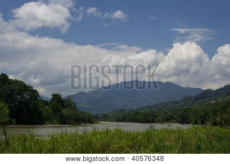 River With Mountains And Clouds In Background