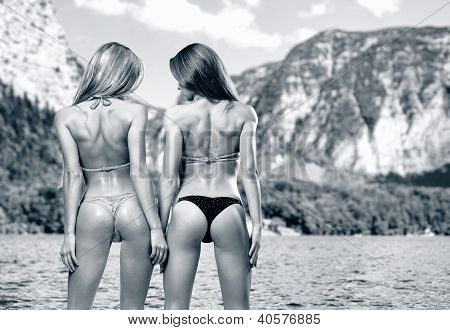 Two Athletic Girl Wearing Bikini Posing Over Beautiful Nature Landscape, Black And White Photo