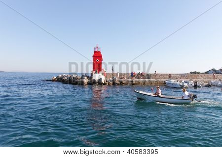 KRK, CROATIA - AUGUST 14, 2011: Tourists enjoying summer around red lighthouse on August 14, 2011 in Krk, Croatia. Krk is the busiest of all northern Croatian islands.