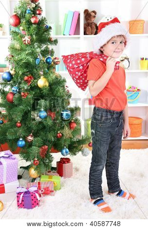Little boy in Santa hat stands near Christmas tree holding bag with gifts