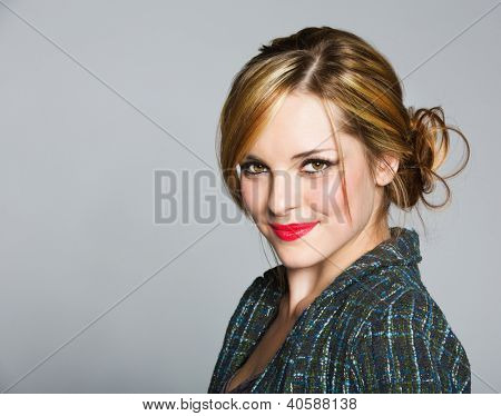 beautiful business woman with blond hair in a bun wearing a tweed jacket and red lipstick on grey studio background