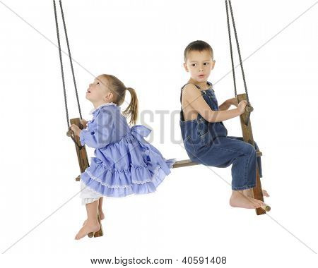 2 preschooler playing on an old wooden, antique 2-person, pump swing together.  The girl is looking up to the top of the ropes, while the brother looks back a bit worried.  On a white background.