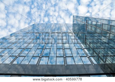 Blue glass office building against blue cloudy sky
