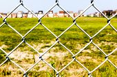 stock photo of chain link fence  - Chain link fence against a green grass and houses in the background - JPG