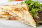 stock photo of ooze  - Bacon & Cheese Toastie served with salad on a white background. Close up.