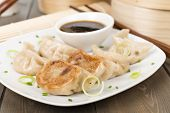 image of dipping  - Yaki-Gyoza - Japanese pan-fried dumplings served with a soy based dipping sauce. Dark wood background.