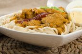 foto of ayam  - Dry Curry Mee - Malaysian chicken curry with coconut milk and noodles on a woven mat.