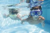 two children diving in masks underwater in pool