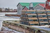picture of lobster trap  - Winter view of lobster traps stacked up on the wharf of French River - JPG