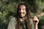 stock photo of rastafari  - hippy preparing rolling and smoking marijuana joint  - JPG