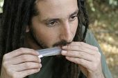 image of rastafari  - hippy preparing rolling and smoking marijuana joint  - JPG
