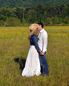 stock photo of denim wear  - Young couple embrace in a field of yellow flowers - JPG