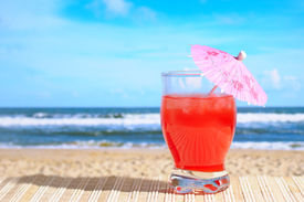 stock photo of beach party  - A glass of cocktail with umbrella at the Beach - JPG