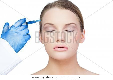Content young model on white background having botox injection