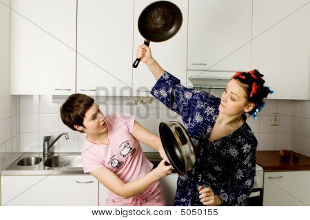 Young Women Fighting In The Kitchen With Pans