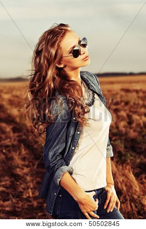 Pretty young woman posing outdoor at sunset.
