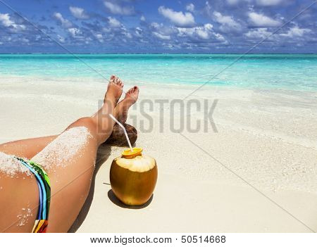 Green Coconut And Legs Of A Young Girl