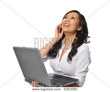 Joven asiática riendo y sosteniendo un ordenador portátil