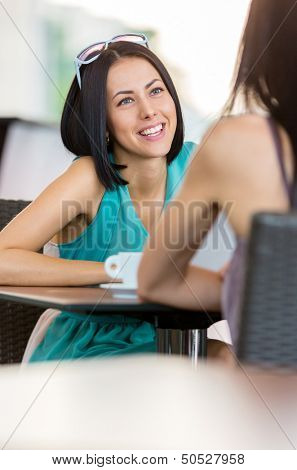Girl wearing blue dress and sunglasses sits at the table of the bar and talks with friend