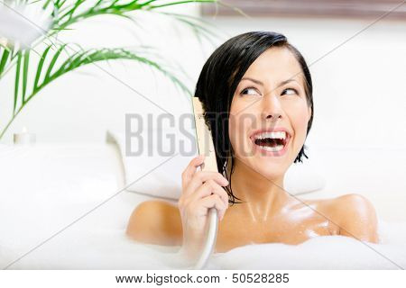 Lady lying in bathtub with suds plays with shower head like phone and relaxes