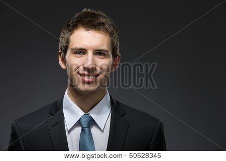 Front view of smiley business man in dark suit with black tie. Concept of professionalism and success in business