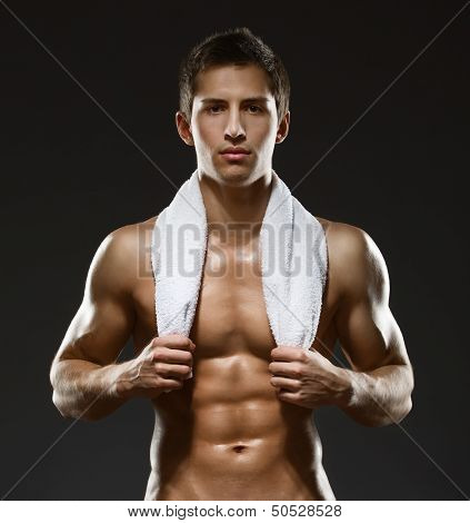Half-length portrait of naked sportsman with towel, isolated on black