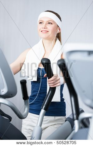 Young woman training on simulators in gym
