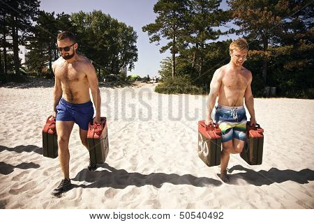 Tough Athletes Doing Workout On Beach With Jerrycans