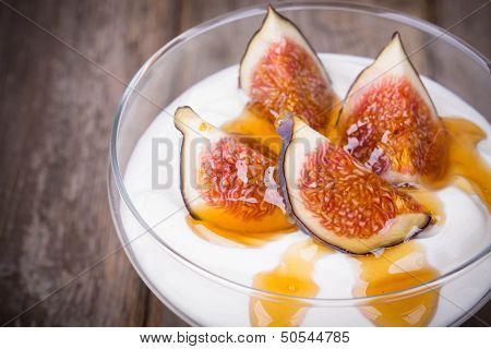Greek yogurt with figs and honey, in a glass bowl over old wood background. Vintage effect with intentional vignette