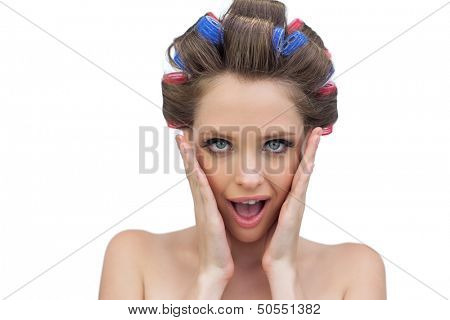 Astonished young model in hair rollers posing on white background