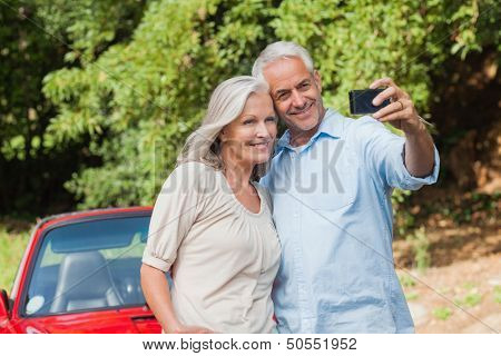 Cheerful mature couple taking pictures of themselves leaning against their cabriolet