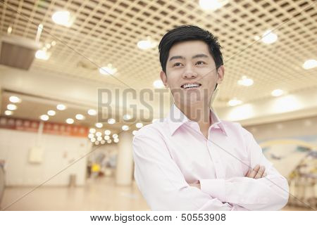 Portrait of young businessman in button down shirt with arms crossed, indoors