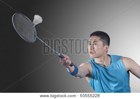 Young man playing badminton, hitting