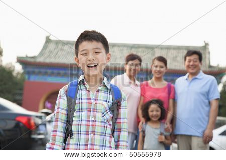 Portrait of boy with his family in the background