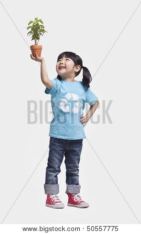 Little girl holding potted plant above her head, studio shot