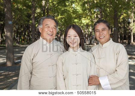 Granddaughter with grandparents practicing Tai Chi
