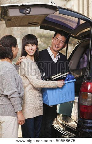 Family unpacking minivan for college, Beijing