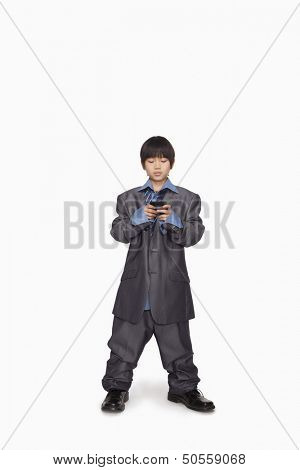 Boy dressed up as businessman checking cell phone