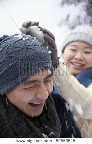 Young Couple Having a Snowball Fight