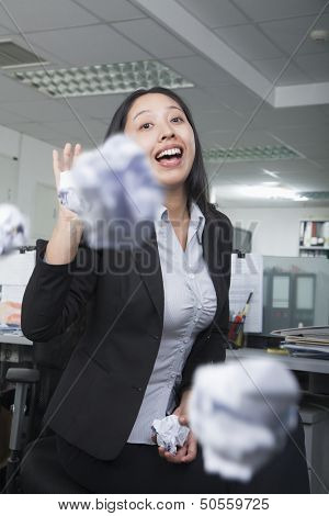 White-collar worker throwing paper in office