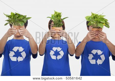 Three people holding plants, obscuring faces, studio shot