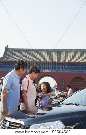 Grandparents and granddaughter standing next to the car and looking at the map