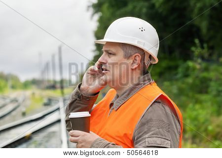 Worker with a coffee and cell phone on the railway