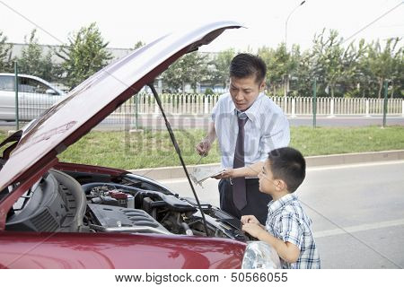 Father and Son Check the Oil on Their Car