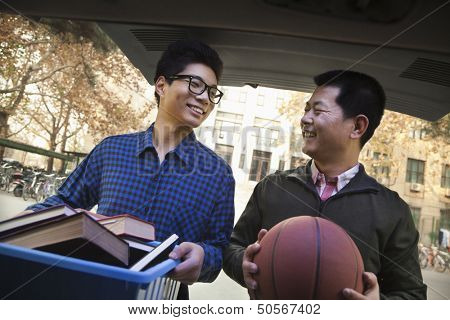 Father and Son in back of car in front of dormitory